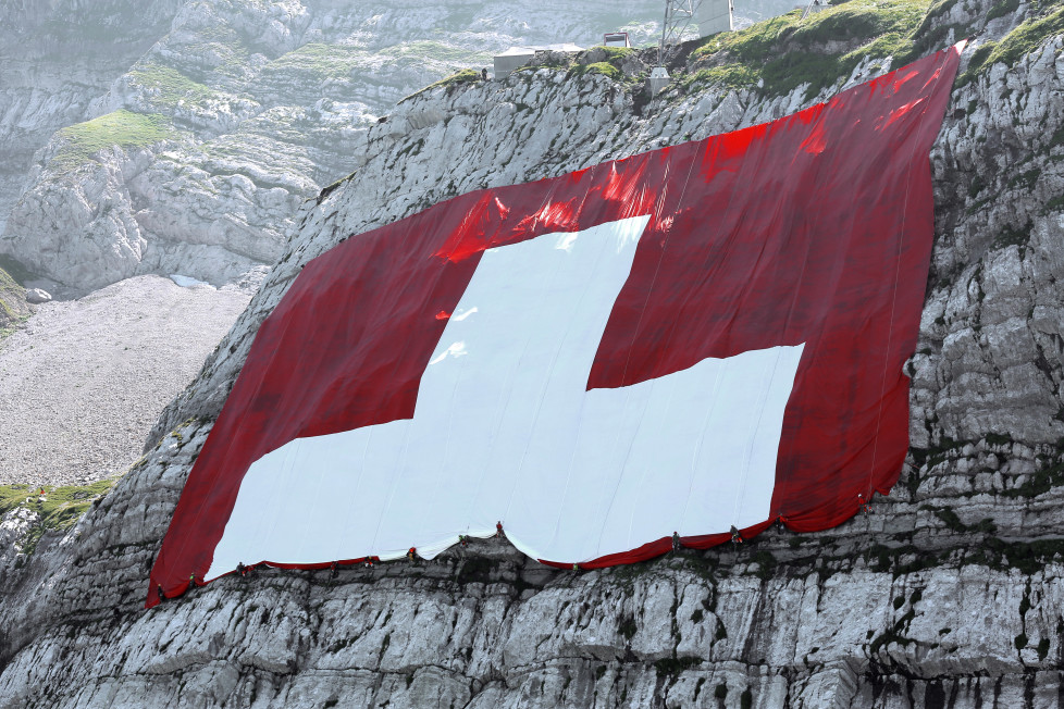 JAHRESRUECKBLICK 2015 - JULI - Workers furl up the world's largest Swiss flag at the ruggedly rock face of the mountain Saentis in Schwaegalp, eastern Switzerland, Friday, July 31, 2015. The flag measures 80 meters to 80 meters and is the world's largest Swiss flag. Saturday 1 August Switzerland is celebrating the national holiday. (KEYSTONE/Pascal Bloch)