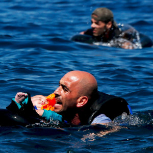 "A Syrian refugee holding a baby swims towards the Greek island of Lesbos, September 12, 2015. Alkis Konstantinidis: Another inflatable boat packed with dozens of migrants and refugees heading towards the shore. That's what I noticed in the distance. The sea was calm and they were cheering on the dinghy. Suddenly, some 200 metres away, the rear of the boat deflated for no obvious reason, and people started falling into the sea. Screams replaced cheers as they frantically tried to stay afloat on life tubes, or by clinging on to the boat. Those who could swim tried to help those who couldn't. As this dramatic scene unfolded and people drifted away from each other, the biggest challenge was to capture as many of the different scenes as I could. There were people falling overboard; two men trying to keep their friend afloat; a man still on the boat lifting his child in the air; another man, nearing collapse from exhaustion, swimming towards the shore; volunteers rushing towards the boat. In this hectic moment, one man, tense and yelling really loudly, caught my eye so I shot some frames. Later, as he tried to catch his breath on the beach, I asked him where he was from. ""Syria,"" he told me before heading towards a volunteer holding a baby. The distance of the shot hadn't allowed me to see the details of the picture clearly. It was only when I began editing that I could make out the tiny head of a baby in a life tube, and the screaming man trying to keep himself and the baby above water. Everything I cover, from riots to politics and sports, trains me to be on the alert and try to get the best from what I am shooting. I learned from this experience that disaster can occur even in what appears to be the calmest of situations. Looking back, the most memorable moment was when I opened the picture and saw the baby, who looked fast asleep as if in a cradle - dreaming or listening to a lullaby. REUTERS/Alkis Konstantinidis SEARCH ""STORY-YEAR"" FOR ALL 14 PICTURES - R"