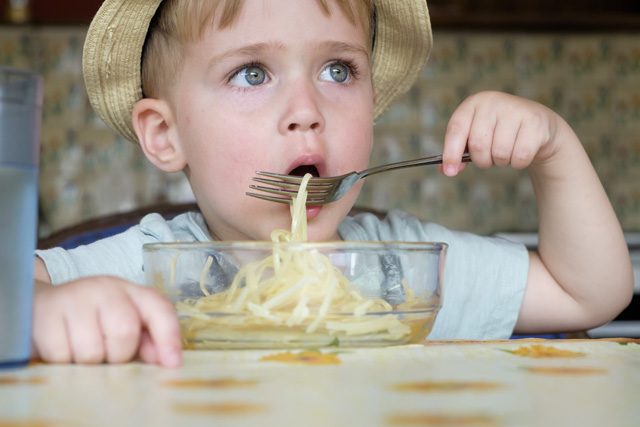 Portrait of little boy eating spaghetti