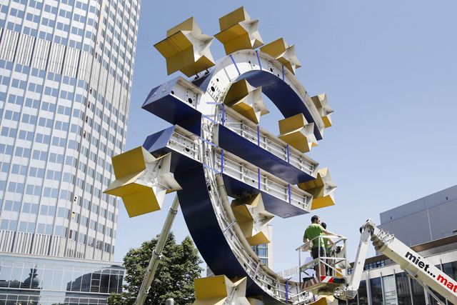 Two workers stand on a lifting platform during renovation works at the Euro sculpture in front of the old European Central Bank in Frankfurt, Germany, Monday, July 6, 2015. The sculpture will be renovated during the next four days. (AP Photo/Michael Probst)