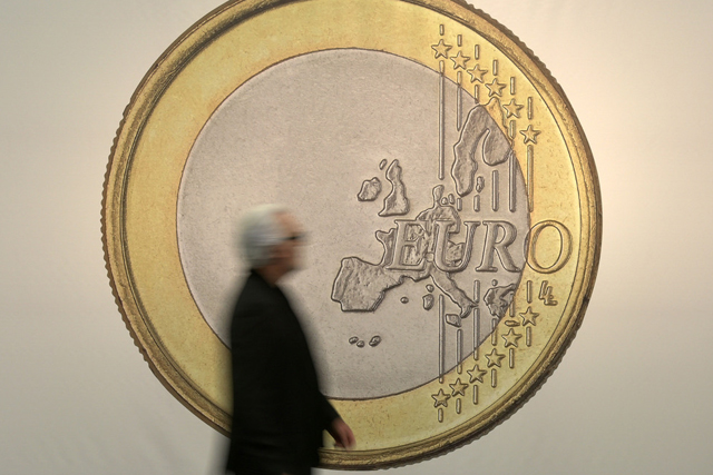 "A man passes the artwork ""Euro"" by artist group Superflex at the art fair in Cologne, Germany, Thursday, April 16, 2015. (AP Photo/Martin Meissner)"