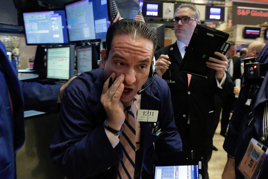 Trader Tommy Kalikas, center, works on the floor of the New York Stock Exchange, Thursday, April 28, 2016. Stocks are opening broadly lower on Wall Street as traders look over the latest batch of earnings and deal news. (AP Photo/Richard Drew)