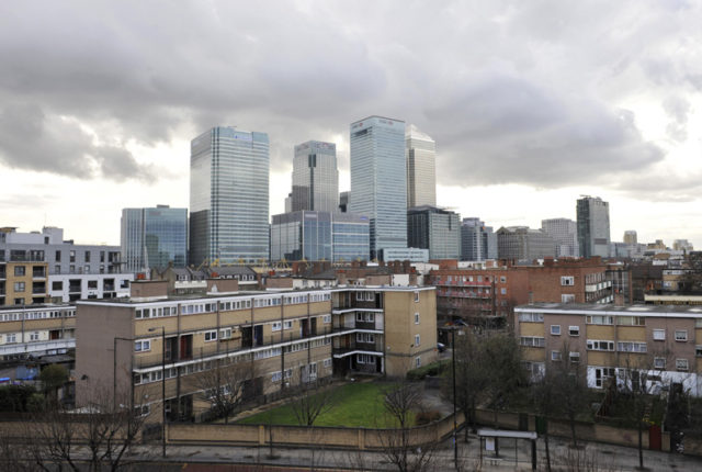 The buildings of the Canary Wharf financial district tower over Poplar, in East London March 27, 2010. Residents of the decaying Robin Hood Gardens estate, where grimy windows punctuate concrete, prison-like corridors, say they feel no connection with those living a short walk away in the luxury Canary Riverside complex. Photograph taken on March 27, 2010.    REUTERS/Jas Lehal    (BRITAIN - Tags: POLITICS ELECTIONS) - RTR2CQ4J