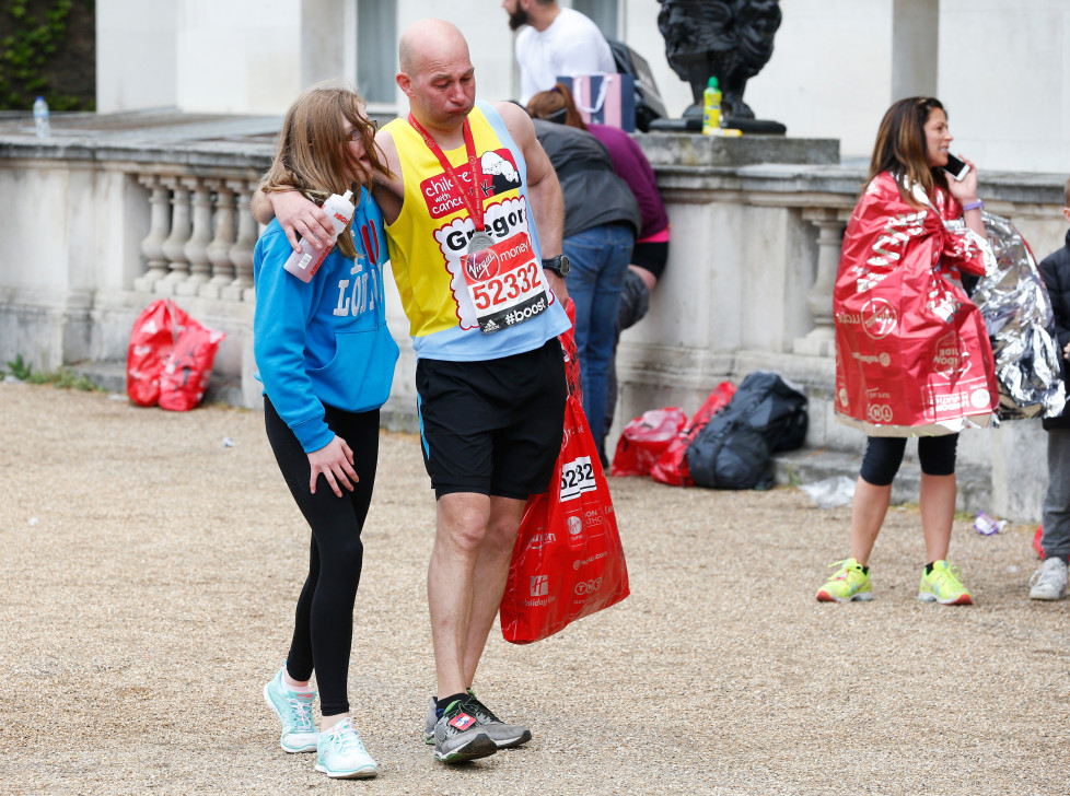 A runner gets a little help after finishing the London Marathon, April 26, 2015. REUTERS/Cathal McNaughton - RTX1AC4P