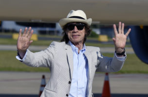 British rock star and lead vocalist of The Rolling Stones, Mick Jagger, waves upon arrival in Montevideo on February 15, 2016, on the eve of their presentation within the America Latina Ole Tour.   AFP PHOTO / PABLO PORCIUNCULA / AFP PHOTO / PABLO PORCIUNCULA
