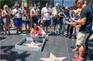 "This Tuesday, July 19, 2016 photo provided by Nick Stern shows a six-inch high, concrete-appearing 'wall,' created by an artist known as Plastic Jesus, surrounding the Hollywood Walk of Fame star of Donald Trump in Los Angeles. It appeared Tuesday, the day the former reality TV star and entrepreneur secured the Republican nomination for president. Tourists snapped photos of the wall, topped with razor wire and plastered with ""keep out"" signs. The tiny wall was gone by Wednesday morning. (Nick Stern via AP)"