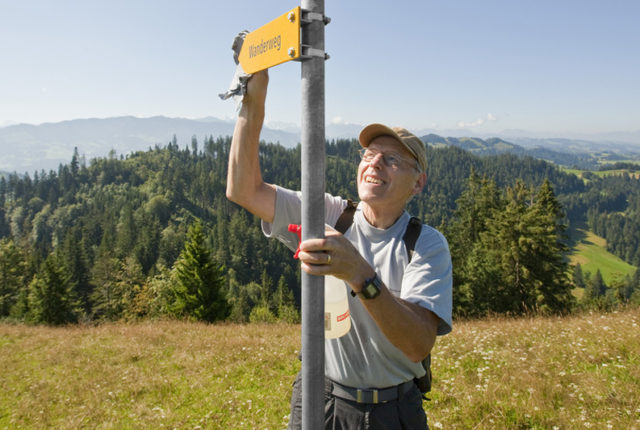 Roland Jakob, the Napf region's district manager of the Bernese Hiking Trails Association BWW, cleans a hiking trail signpost near Trub in in the canton of Berne, Switzerland, pictured on August 6, 2009. (KEYSTONE/Alessandro Della Bella)  Roland Jakob, Bezirksleiterleiter der Region Napf der Berner Wanderwege BWW, putzt am 6. August 2009 bei Trub im Kanton Bern einen Wegweiser fuer Wanderwege. (KEYSTONE/Alessandro Della Bella)