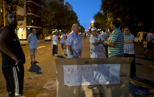 "Residents of the Almagro neighborhood block a road, where they placed a sign that reads in Spanish: ""We want light and water,"" as they protest the fourth day in a row without electricity in Buenos Aires, Argentina, Thursday, Feb. 18, 2016. The city's energy system has not been able to cope with the summer heat wave, prompting some residents to block streets in protest. Furthermore, the government began rationing electricity on Thursday, affecting thousands of homes and businesses in the capital and surrounding towns. (AP Photo/Natacha Pisarenko)"
