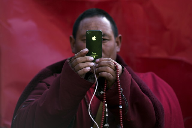 A Tibetan Buddhist monk takes pictures with his smartphone of a daily chanting session at a Buddhist laymen lodge during the Utmost Bliss Dharma Assembly, the last of the four Dharma assemblies at Larung Wuming Buddhist Institute in remote Sertar county, Garze Tibetan Autonomous Prefecture, Sichuan province, China early October 30, 2015. The eight-day gathering of people chanting mantras and listening to teachings of monks starts every year around the 22nd of the ninth month on Tibetan calendar, the great day of Buddha's Descending from Tushita Heavens. The Larung Wuming Buddhist Institute, located some 3700 to 4000 metres above the sea level was founded in 1980 by Khenpo Jigme Phuntsok, an influential lama of Nyingma sect of Tibetan buddhism with only around 30 students but is now widely known as one of the biggest centres to study Tibetan Buddhism in the world. Picture taken October 30, 2015. REUTERS/Damir Sagolj TPX IMAGES OF THE DAY - RTX1UHT7