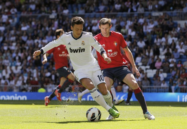 Real Madrid's Mesut Ozil from Germany, left, in action with Osasuna's Ruben, right, during a Spanish La Liga soccer match at the Santiago Bernabeu stadium in Madrid, Spain, Saturday, June 1, 2013. (AP Photo/Andres Kudacki)