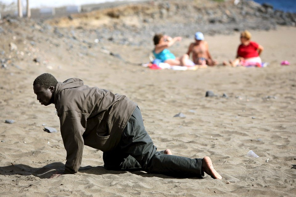 """A would-be immigrant crawls after his arrival on a makeshift boat on the Gran Tarajal beach in Spain's Canary Island, in this May 5, 2006 file photo. Italy stepped up calls for a change to European asylum rules on Sunday as neighbouring states tightened border controls, turning back African migrants and leaving hundreds stranded at the frontier in northern Italy.  REUTERS/Juan Medina/Files ATTENTION EDITORS - THIS PICTURE IS PART OF THE PACKAGE """"IN PLAIN SIGHT"""". TO FIND ALL 9 IMAGES SEARCH 'MIGRANT EUROPEAN'.      TPX IMAGES OF THE DAY           TPX IMAGES OF THE DAY"""