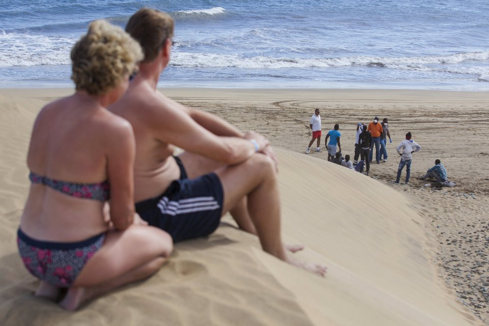 """Tourists look at would-be immigrants at the Maspalomas beach, on Gran Canaria in Spain's Canary Islands, in this November 5, 2014 file photo. Italy stepped up calls for a change to European asylum rules on Sunday as neighbouring states tightened border controls, turning back African migrants and leaving hundreds stranded at the frontier in northern Italy.  REUTERS/Borja Suarez/Files ATTENTION EDITORS - THIS PICTURE IS PART OF THE PACKAGE """"IN PLAIN SIGHT"""". TO FIND ALL 9 IMAGES SEARCH 'MIGRANT EUROPEAN'.      TPX IMAGES OF THE DAY"""