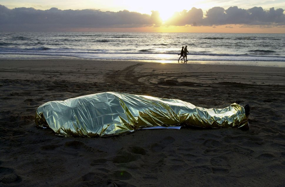"""The body of a dead immigrant, who drowned after his makeshift boat capsized, lies covered on El Matorral beach in Fuerteventura, Spain, as beachgoers walk along in the background, in this January 1, 2003 file photo. Italy stepped up calls for a change to European asylum rules on Sunday as neighbouring states tightened border controls, turning back African migrants and leaving hundreds stranded at the frontier in northern Italy.  REUTERS/Juan Medina/Files ATTENTION EDITORS - THIS PICTURE IS PART OF THE PACKAGE """"IN PLAIN SIGHT"""". TO FIND ALL 9 IMAGES SEARCH 'MIGRANT EUROPEAN'.      TPX IMAGES OF THE DAY"""