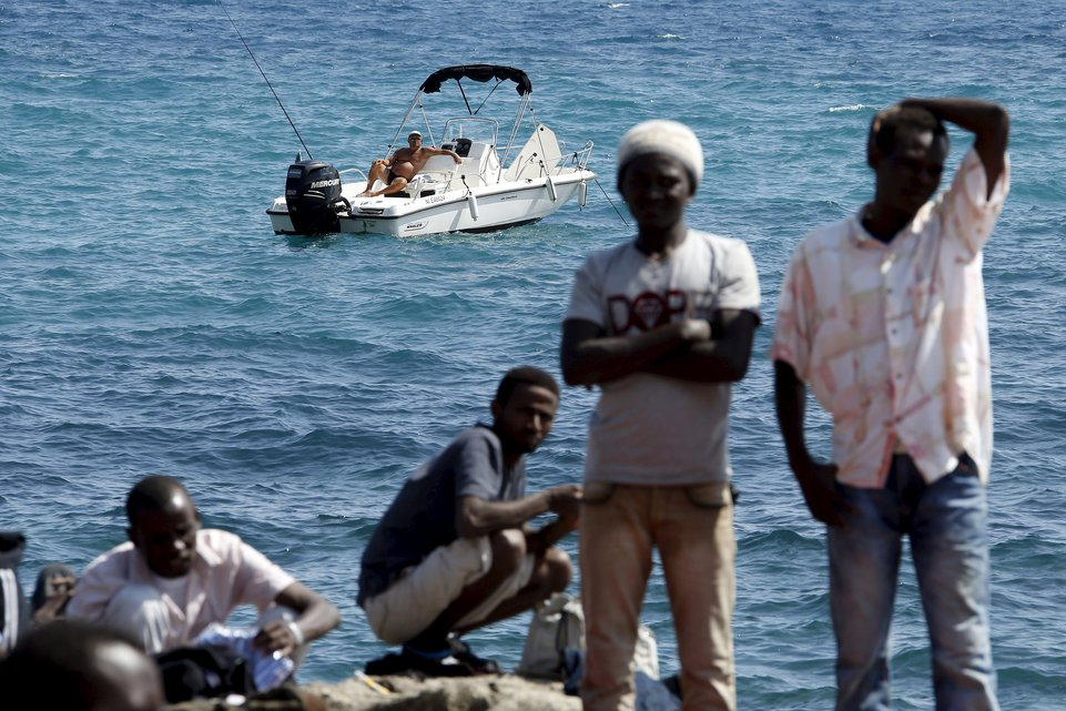 """A man fishes from his boat as a group of migrants gather on the seawall at the Saint Ludovic border crossing on the Mediterranean Sea between Vintimille, Italy and Menton, France, in this June 14, 2015 file photo. Italy stepped up calls for a change to European asylum rules on Sunday as neighbouring states tightened border controls, turning back African migrants and leaving hundreds stranded at the frontier in northern Italy.  REUTERS/Eric Gaillard/Files ATTENTION EDITORS - THIS PICTURE IS PART OF THE PACKAGE """"IN PLAIN SIGHT"""". TO FIND ALL 9 IMAGES SEARCH 'MIGRANT EUROPEAN'.      TPX IMAGES OF THE DAY"""