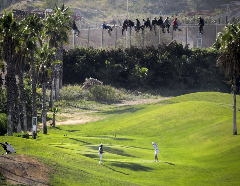 """A golfer hits a tee shot as African migrants sit atop a border fence during an attempt to cross into Spanish territories between Morocco and Spain's north African enclave of Melilla, in this October 22, 2014 file photo. Italy stepped up calls for a change to European asylum rules on Sunday as neighbouring states tightened border controls, turning back African migrants and leaving hundreds stranded at the frontier in northern Italy.  REUTERS/Jose Palazon/Files ATTENTION EDITORS - THIS PICTURE IS PART OF THE PACKAGE """"IN PLAIN SIGHT"""". TO FIND ALL 9 IMAGES SEARCH 'MIGRANT EUROPEAN'."""