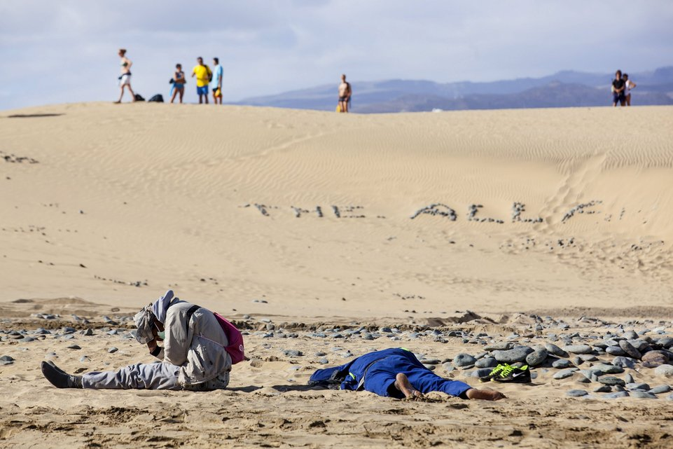 """Two would-be immigrants rest at Maspalomas beach on Gran Canaria in Spain's Canary Islands in this November 5, 2014 file photo. Italy stepped up calls for a change to European asylum rules on Sunday as neighbouring states tightened border controls, turning back African migrants and leaving hundreds stranded at the frontier in northern Italy.  REUTERS/Borja Suarez/Files ATTENTION EDITORS - THIS PICTURE IS PART OF THE PACKAGE """"IN PLAIN SIGHT"""". TO FIND ALL 9 IMAGES SEARCH 'MIGRANT EUROPEAN'."""