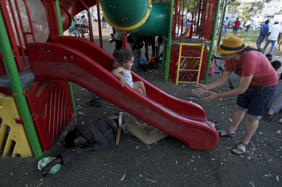 """A Sudanese migrant sleeps under a slide as an Israeli girl slides down it at Levinsky park in South Tel Avi, in this June 16, 2012 file photo. Italy stepped up calls for a change to European asylum rules on Sunday as neighbouring states tightened border controls, turning back African migrants and leaving hundreds stranded at the frontier in northern Italy.  REUTERS/Baz Ratner/Files ATTENTION EDITORS - THIS PICTURE IS PART OF THE PACKAGE """"IN PLAIN SIGHT"""". TO FIND ALL 9 IMAGES SEARCH 'MIGRANT EUROPEAN'."""