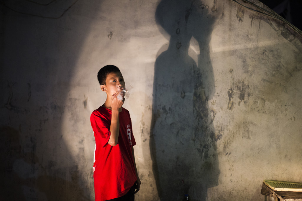 Andika Prasetyo, who smokes about a pack a day, has a smoke outside an internet cafe on February 16, 2015. (Photo By: Michelle Siu)