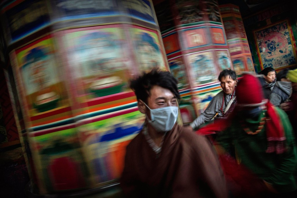 SERTAR, CHINA - OCTOBER 30: Tibetan Buddhist nomads rush passed a large prayer wheel outside the annual Bliss Dharma Assembly at the Larung Wuming Buddhist Institute on October 30, 2015 in Sertar county, in the remote Garze Tibetan Autonomous Prefecture, Sichuan province, China. The last of four annual assemblies, the week long annual gathering takes place in the ninth month of the Tibetan calendar and marks Buddha's descent from the heavens. Located high in the mountains of Sichuan, the Larung Wuming Buddhist Institute was founded in 1980 by an influential lama of the Nyingma sect and is widely regarded as the world's largest and most influential centres for Tibetan Buddhist studies. The school is home to thousands of monks and nuns and is popular for followers from all over the Tibetan areas and other parts of China. (Photo by Kevin Frayer/Getty Images)