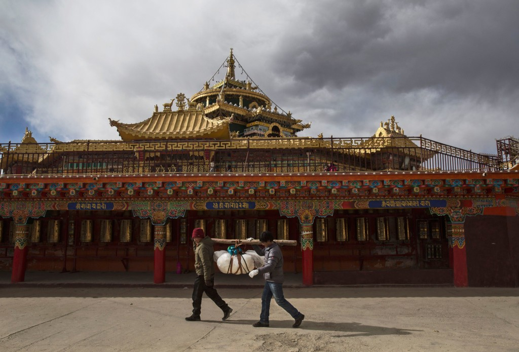 SERTAR, CHINA - OCTOBER 30: Tibetan Buddhists carry the body of a relative as they circumbulate a monastery before sky burial at the Larung Wuming Buddhist Institute on October 30, 2015 in Sertar county, in the remote Garze Tibetan Autonomous Prefecture, Sichuan province, China. The last of four annual assemblies, the week long annual gathering takes place in the ninth month of the Tibetan calendar and marks Buddha's descent from the heavens. Located high in the mountains of Sichuan, the Larung Wuming Buddhist Institute was founded in 1980 by an influential lama of the Nyingma sect and is widely regarded as the world's largest and most influential centres for Tibetan Buddhist studies. The school is home to thousands of monks and nuns and is popular for followers from all over the Tibetan areas and other parts of China. (Photo by Kevin Frayer/Getty Images)