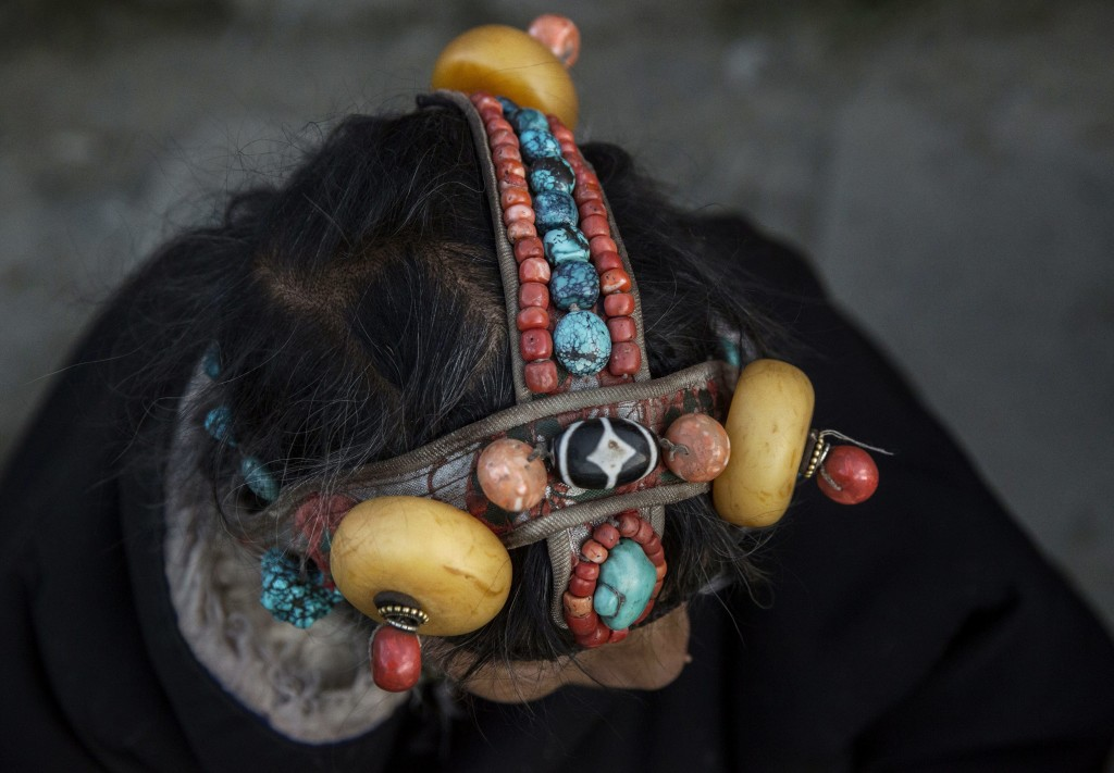 SERTAR, CHINA - NOVEMBER 1: A Tibetan Buddhist woman wears traditional stones in her hair at the annual Bliss Dharma Assembly at the Larung Wuming Buddhist Institute on November 1, 2015 in Sertar county, in the remote Garze Tibetan Autonomous Prefecture, Sichuan province, China. The last of four annual assemblies, the week long annual gathering takes place in the ninth month of the Tibetan calendar and marks Buddha's descent from the heavens. Located high in the mountains of Sichuan, the Larung Wuming Buddhist Institute was founded in 1980 by an influential lama of the Nyingma sect and is widely regarded as the world's largest and most influential centres for Tibetan Buddhist studies. The school is home to thousands of monks and nuns and is popular for followers from all over the Tibetan areas and other parts of China. (Photo by Kevin Frayer/Getty Images)