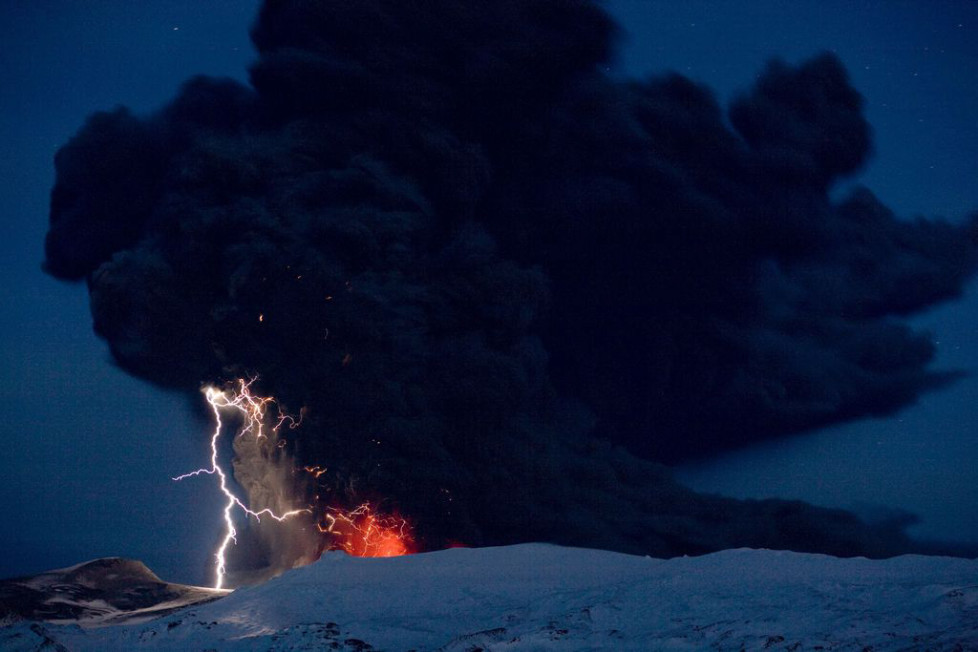 Lighting seen amid the lava and ash erupting from the vent of the Eyjafjallajokull volcano in central Iceland early morning Sunday April 18 2010 as it continues to vent into the skies over Europe. Low-energy lightning is sometimes active during eruptions, arcing between particles as they exit the volcanic vent at around 100 metres per second. The dramatic volcanic eruption which has closed Europe's airspace for days has entered a new phase - producing less smoke but bubbling with lava and throwing up chunks of molten rock. (KEYSTONE/AP Photo/ Jon Pall Vilhelmsson)