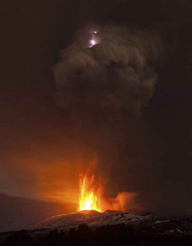 In this picture made available Friday, Dec. 4, 2015, lightning is seen in the cloud of smoke during an eruption of Mt. Etna, near Catania, Italy, Thursday Dec. 3, 2015. Mt. Etna is Europe's most active volcano at 3,350 meters (10,990 feet) and erupts quite frequently. (AP Photo/Salvatore Allegra)