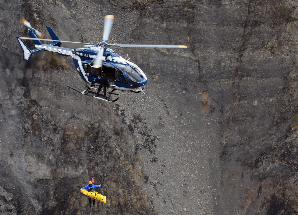"A French gendarmerie's helicopter lifts an investigator on March 26, 2015 near scattered debris on the crash site of the Germanwings Airbus A320 that crashed in the French Alps above the southeastern town of Seyne. The young co-pilot of the doomed Germanwings flight that crashed on March 24, appears to have ""deliberately"" crashed the plane into the French Alps after locking his captain out of the cockpit, but is not believed to be part of a terrorist plot, French officials said on March 26, 2015. AFP PHOTO / ANNE-CHRISTINE POUJOULAT / AFP / ANNE-CHRISTINE POUJOULAT"