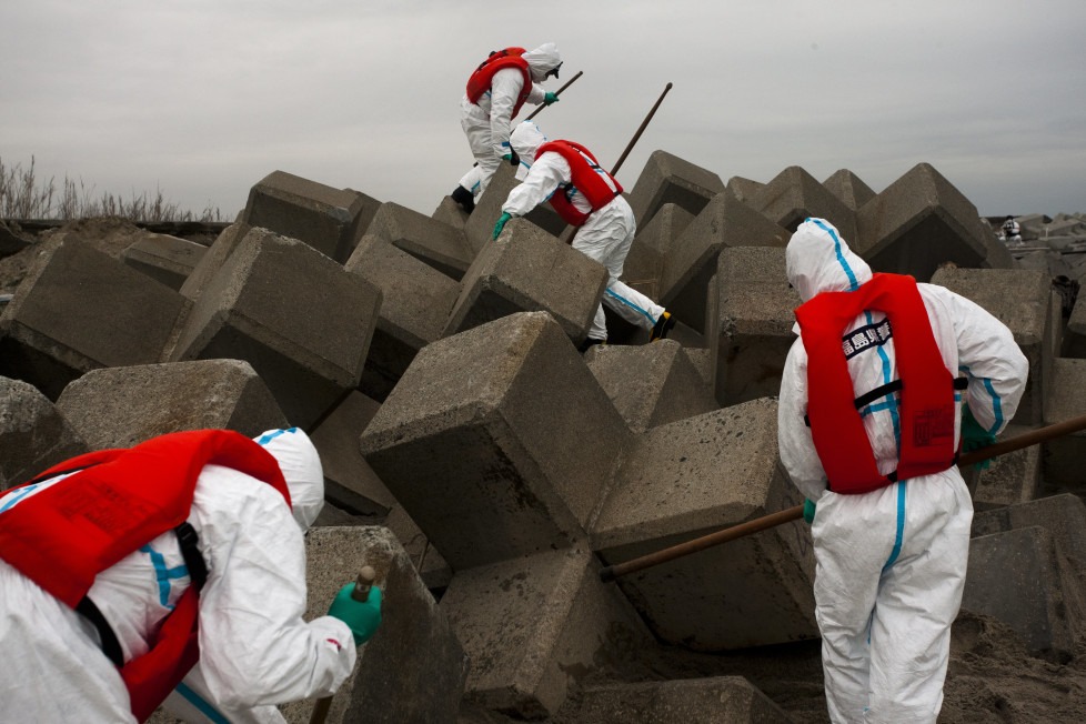 Japan, Namie, 2012. Police search for remains of missing people inside the nuclear exclusion zone near the damaged Daiichi nuclear power plant one year after the Tsunami hit the north east coast of Japan.