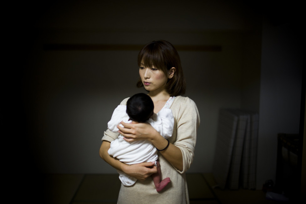 Japan, Tokyo, 2011 Sachiko Masuyama (30) now in her new home in Shinonome housing for government workers. She discovered she was pregnant, two days before the quake and now hold her new born.