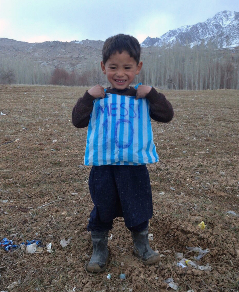 This photograph taken on January 24, 2016 and provided by the family of Afghan boy and Lionel Messi fan Murtaza Ahmadi, 5, with his plastic bag jersey in Jaghori district of Ghazni province. A five-year-old Afghan boy has become an internet star after pictures went viral of him wearing an Argentina football shirt made out of a plastic bag, complete with his hero Lionel Messi's name. AFP PHOTO / AFP / STR