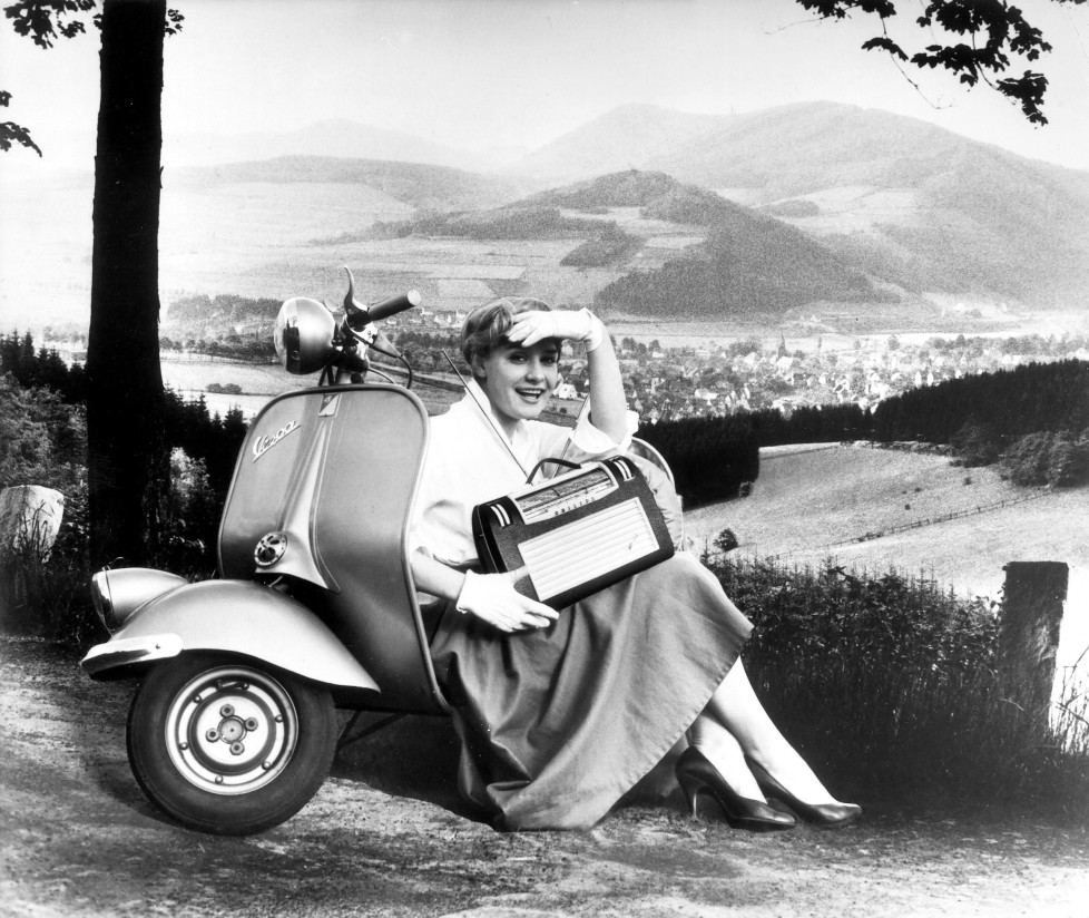 """(GERMANY OUT) A young girl with a portable radio and a motor-scooter """"Vespa - Piaggio"""" - 1956 (Photo by ullstein bild/ullstein bild via Getty Images)"""