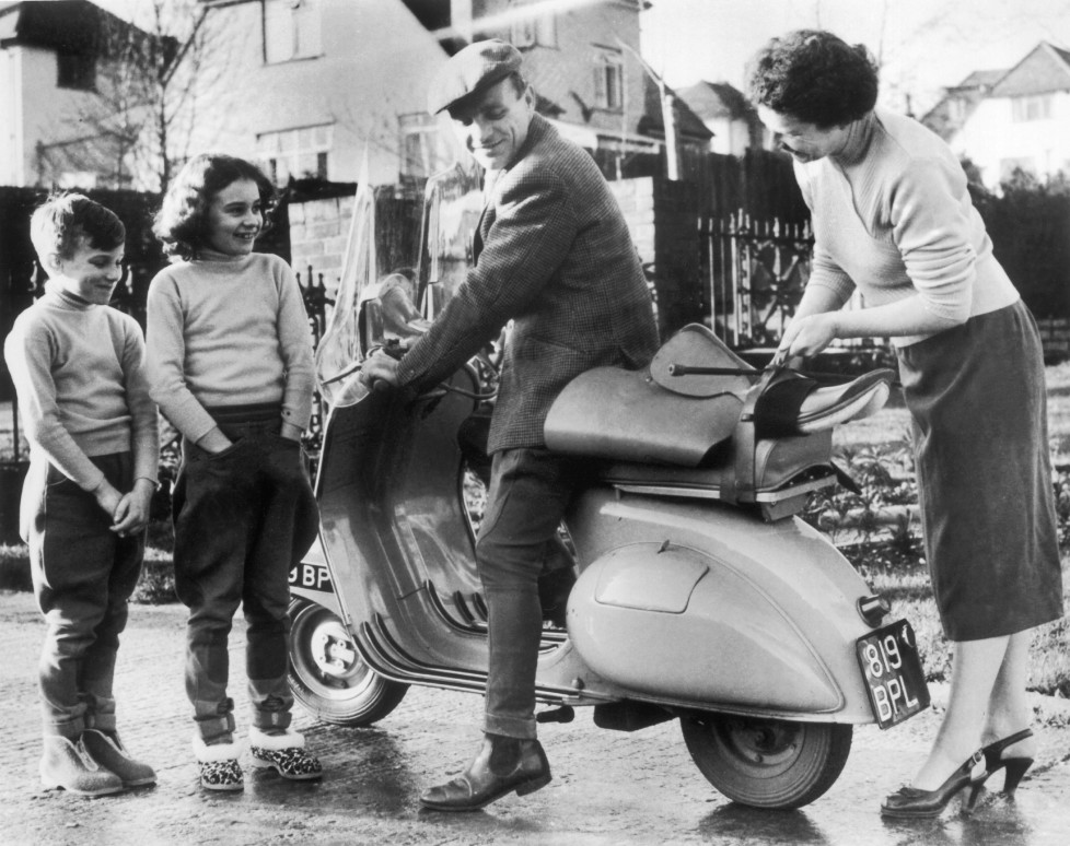 UNITED KINGDOM - JANUARY 09: January 9, 1957: A jockey by the name of Harry SPRAGUE climbing on his VESPA moped to go to the racetrack, while his children and wife stood by. He thought he was taking good measures in view of the possible oil shortage that was being talked about at that time. (Photo by Keystone-France/Gamma-Keystone via Getty Images)