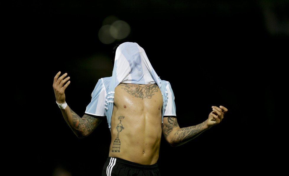 In this Tuesday, March 29, 2016 photo, Argentina's Marcos Rojo pulls his jersey over his head after missing an opportunity to score against Bolivia, during a 2018 World Cup qualifying soccer match, in Cordoba, Argentina. Gabriel Mercado scored in the 19th minute and Lionel Messi made it 2-0 in the 29th on a penalty to lead the Argentines to an easy victory. (AP Photo/Natacha Pisarenko)