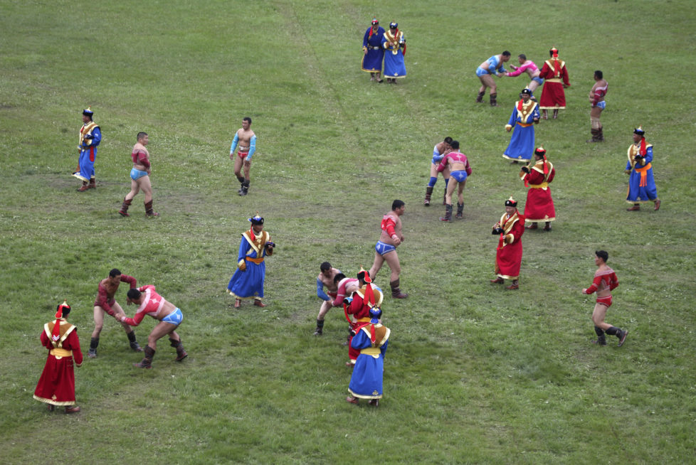 Mongolian wrestlers compete during wrestling competition at the annual Naadam Festival in Ulan Bator, July 11, 2012. Naadam is the biggest event in the Mongolian calendar held from July 11 to 13, on the anniversary of the Mongolian revolution of 1921. Concerts, fairs and traditional sports like wrestling, archery and horse racing are held during the celebration. REUTERS/B.Rentsendorj (MONGOLIA - Tags: SOCIETY SPORT WRESTLING) - RTR34TJ4