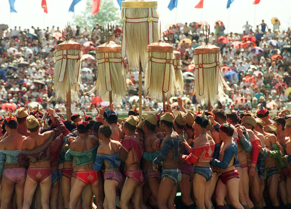 "Mongolian wrestlers circle the state banners in Ulan Bator during the annual traditional summer festival of Nadaam, July 11. Tens of thousands of Mongolians from all corners of the vast land-locked country descended on the capital to visit relatives and friends and watch traditional dances and competitions in the ""three manly sports"" of horse-racing, archery and wrestling. MONGOLIA - RTR5G3S"