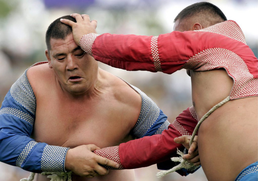 epa01063708 Mongolian wrestlers in traditional attire grapple during wrestling competitions as referees look on during the Naadam festival at the National Stadium in Ulaanbaatar, Mongolia, 11 July 2007. Mongolia is celebrating the Naadam festival from the 11-13 July 2007, the most important festival of the year, with horseracing, wrestling and archery - known as the three 'manly sports'. EPA/MICHAEL REYNOLDS