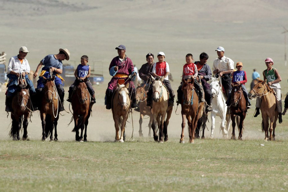 epa01061682 Mongolian children and adults ride to the start of a 23 kilometre horserace jockeyed by children age four to thirteen, in Atar, Tuv Aimag, Mongolia, 10 July 2007. Mongolia is celebrating the Naadam festival from 11-13 July 2007, the most important festival of the year, with horseracing, wrestling and archery - known as the three 'manly sports'. EPA/MICHAEL REYNOLDS