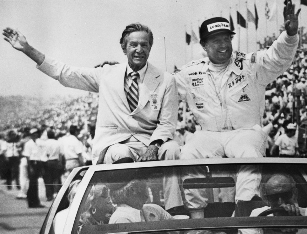 In a May 29, 1977, photo provided by Indianapolis Motor Speedway, Tony Hulman, left, and A.J. Foyt wave to fans during a victory lap after Foyt won his fourth Indianapolis 500 auto race in Indianapolis. (Indianapolis Motor Speedway via AP)