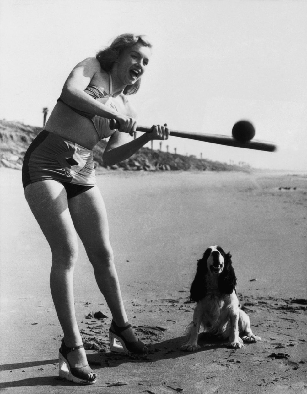 The American actress Marilyn Monroe playing softball in a bathing suit on a beach. USA, 1950s (Photo by Mondadori Portfolio via Getty Images)