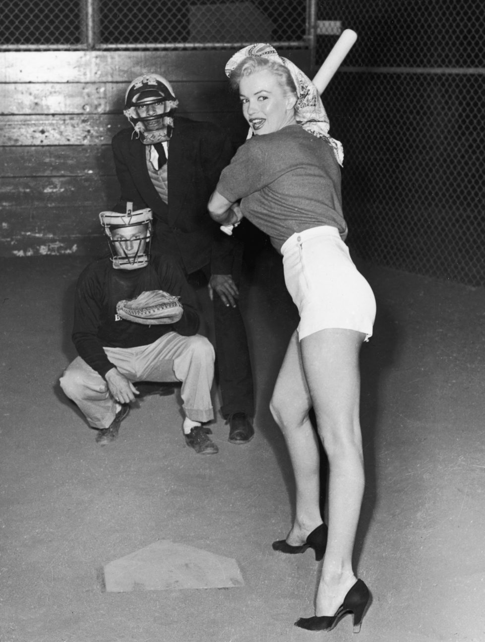 July 1952: American actor Marilyn Monroe (1926 - 1962), wearing shorts and high heels, prepares to swing a baseball bat during a 20th Century Fox Studio baseball league game. Studio employees play umpire and catcher. (Photo by Hulton Archive/Getty Images)