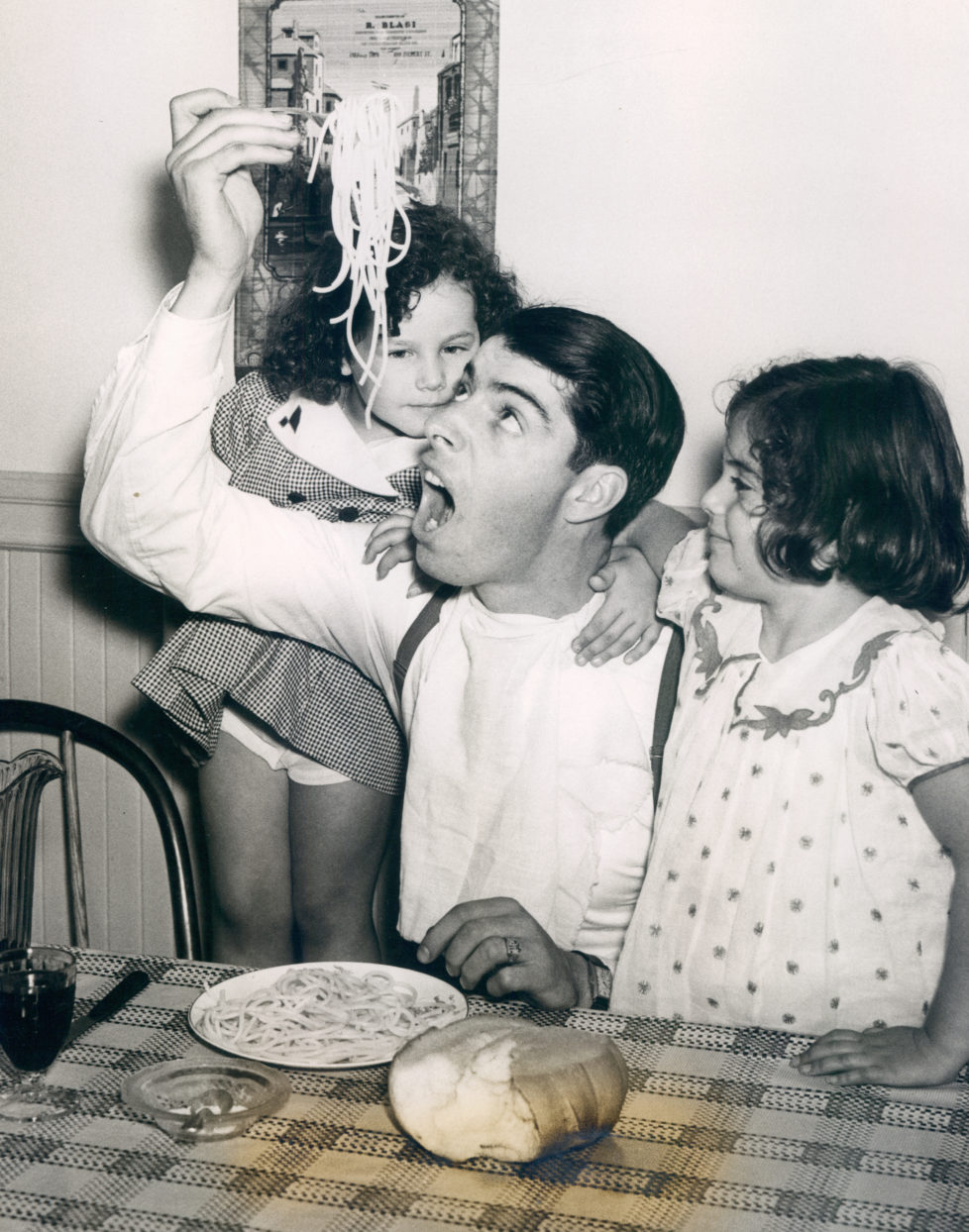 UNSPECIFIED - UNDATED: Joe DiMaggio eating pasta with a couple of young fans. (Photo by Sports Studio Photos/Getty Images)