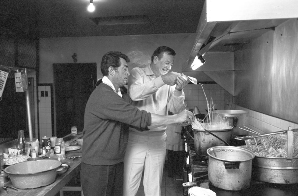 American actors Dean Martin (Dino Paul Crocetti) and John Wayne (Marion Mitchell Morrison) having fun by cooking spaghetti in a break during the shooting of the film The Sons of Katie Elder. 1966 (Photo by Pierluigi Praturlon/Reporters Associati & Archivi/Mondadori Portfolio via Getty Images)