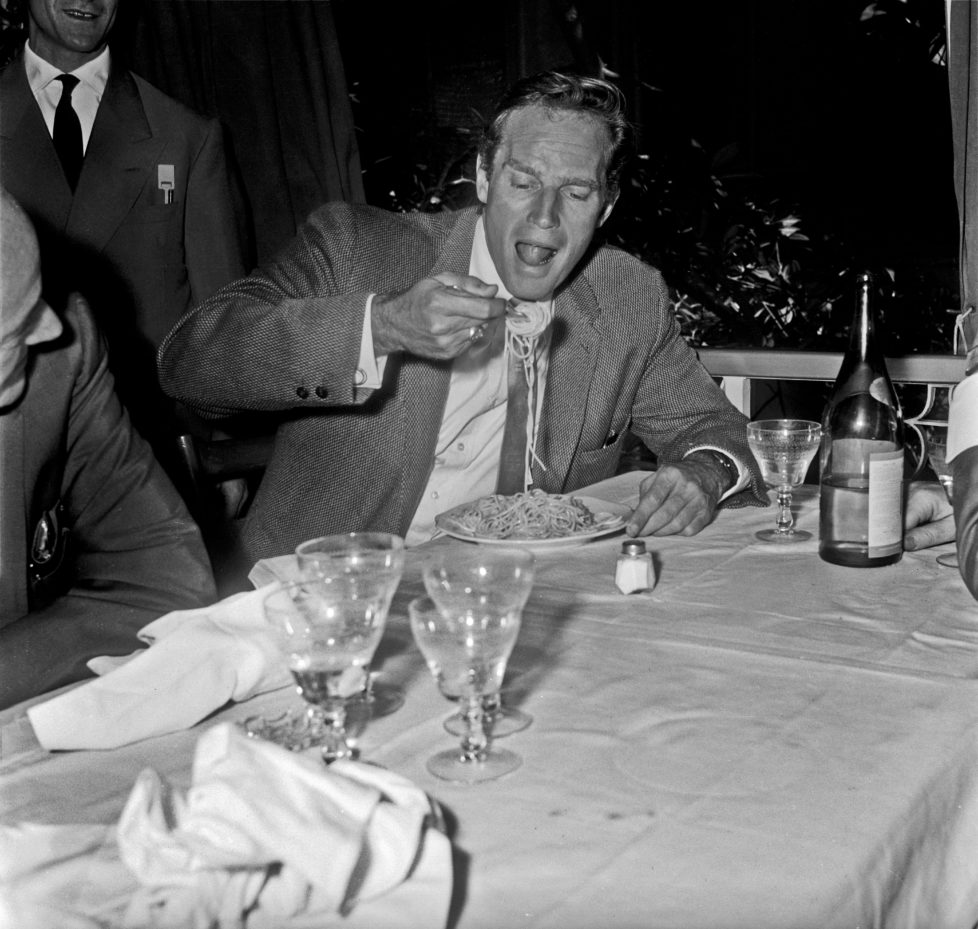 American actor Charlton Heston (John Charles Carter) eating spaghetti in a restaurant. Rome, 1960 (Photo by Reporters Associati & ArchiviMondadori Portfolio via Getty Images)