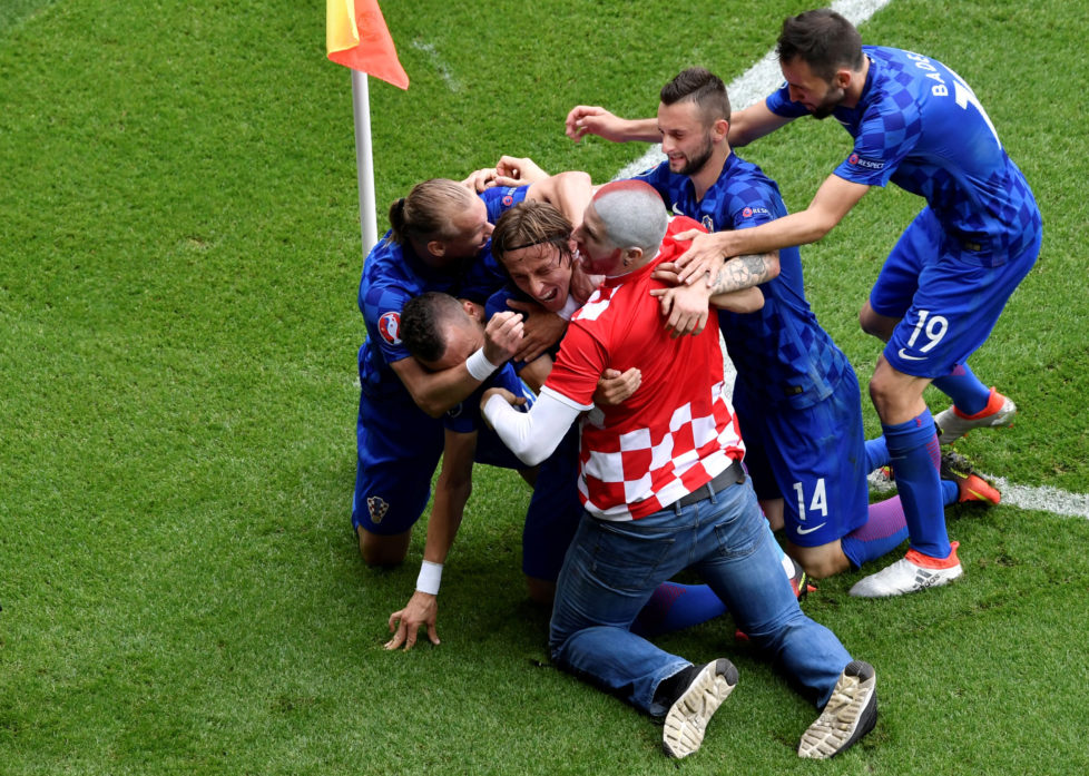 A fan enters onto the pitch to celebrates with Croatia's midfielder Luka Modric and his teammates after Modric scored the team's first goal during the Euro 2016 group D football match between Turkey and Croatia at Parc des Princes in Paris on June 12, 2016. / AFP PHOTO / PHILIPPE LOPEZ