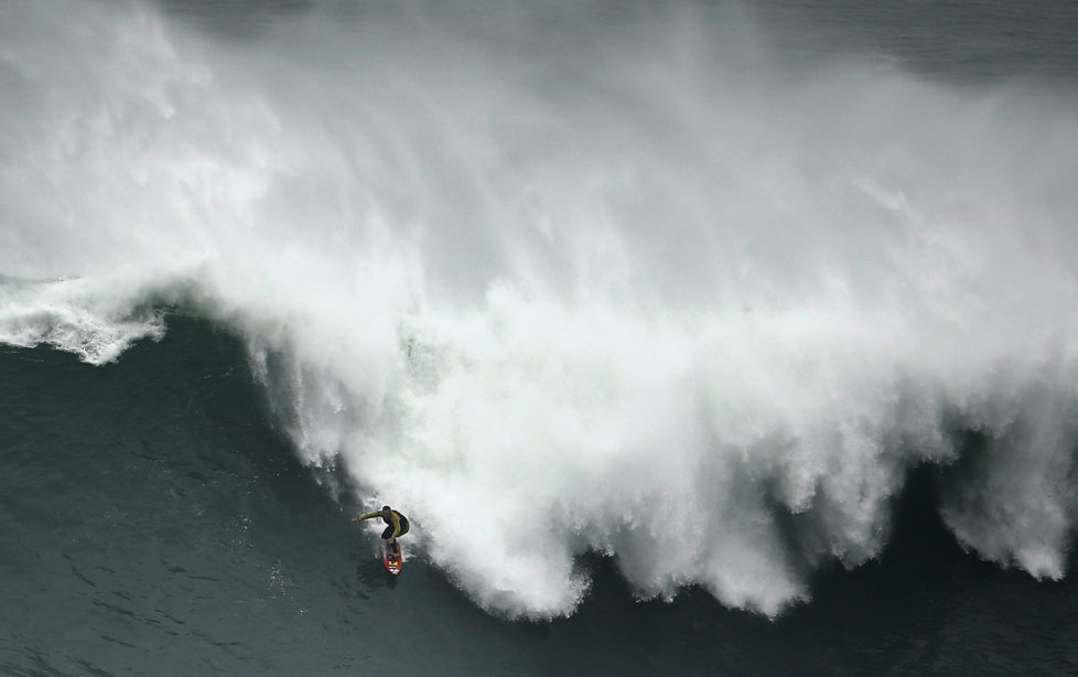 Big-wave surfer Garrett McNamara of the U.S. drops in on a large wave at Praia do Norte, in Nazare November 1, 2013. McNamara, who lives in Haleiwa, Hawaii, won the Biggest Wave title at the 2012 Billabong XXL Big Wave Awards with his world record 78-foot (24-metre) wave ridden at Praia do Norte, Nazare, Portugal on November 1, 2011. McNamara has returned to Nazare because he wants to try to beat the record again. REUTERS/Rafael Marchante (PORTUGAL - Tags: SPORT TPX IMAGES OF THE DAY) - RTX14WO2