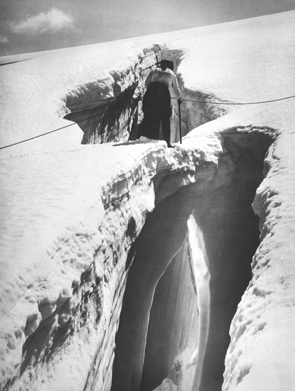 A mountain climber in the Swiss Alps cautiously traverses an ice bridge over a crevasse, Switzerland, circa 1928. (Photo by Underwood Archives/Getty Images)