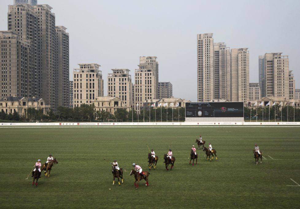 """TIANJIN, CHINA - JULY 17: Chinese players from the Metropolitan Polo Club team, in white, and players from the United States and Great Britain play an exhibiton match at the Tianjin Goldin Metropolitan Polo Club on July 17, 2016 in Tianjin, China. China's rising affluence has nurtured growing interest in polo and other past-times regarded as noble or prestigious by the country's elite. Clubs and international-size polo fields have been built in various cities including Beijing and Shanghai, and on the outskirts of Tianjin, where membership at the exclusive Goldin Metropolitan, China's largest polo club, is by invitation-only and fees can be significant for polo team owners. Increasingly, wealthy Chinese parents are choosing polo and other equestrian activities for their children as a way to bolster their credentials for admission to top-tier universities in the United States and the United Kingdom. While the so-called """"sport of kings"""" became a mainstay in Hong Kong during the era of British rule, polo is a relatively new sport to mainland China. Professional polo players are frequently flown in from countries such as New Zealand and Argentina in order to field competitive matches. Many of the polo clubs in China are tied to luxury real estate developments. (Photo by Kevin Frayer/Getty Images)"""