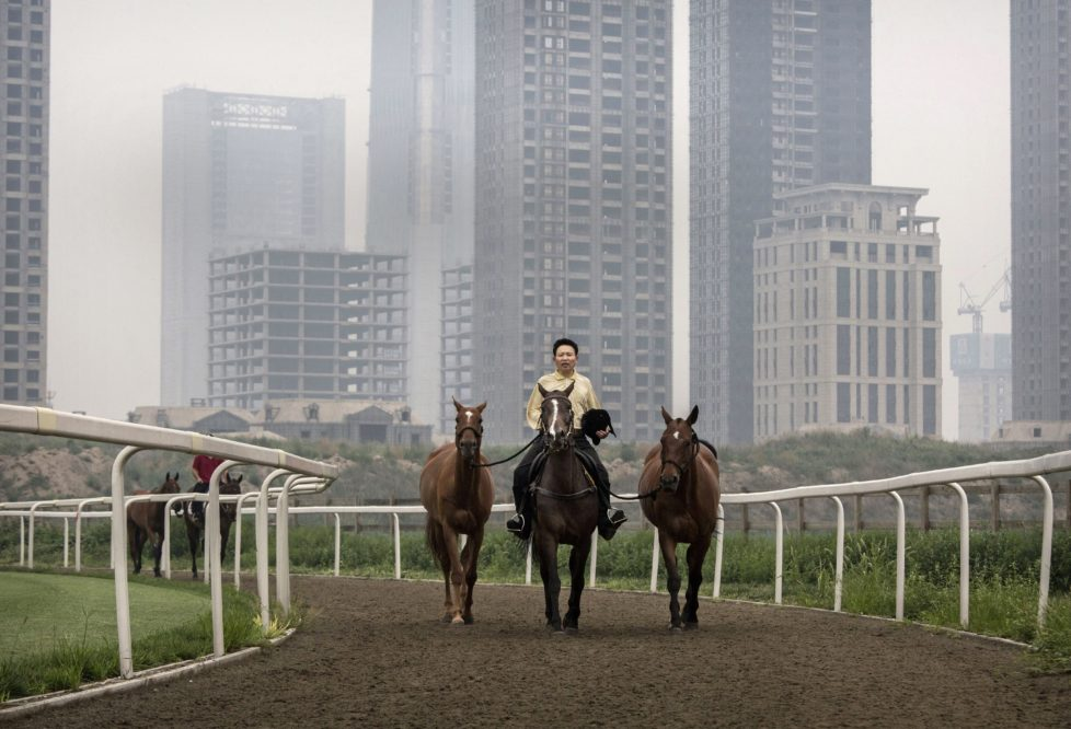 """TIANJIN, CHINA - JULY 17: A Chinese horse trainer exercises polo horses at the Tianjin Goldin Metropolitan Polo Club on July 17, 2016 in Tianjin, China. China's rising affluence has nurtured growing interest in polo and other past-times regarded as noble or prestigious by the country's elite. Clubs and international-size polo fields have been built in various cities including Beijing and Shanghai, and on the outskirts of Tianjin, where membership at the exclusive Goldin Metropolitan, China's largest polo club, is by invitation-only and fees can be significant for polo team owners. Increasingly, wealthy Chinese parents are choosing polo and other equestrian activities for their children as a way to bolster their credentials for admission to top-tier universities in the United States and the United Kingdom. While the so-called """"sport of kings"""" became a mainstay in Hong Kong during the era of British rule, polo is a relatively new sport to mainland China. Professional polo players are frequently flown in from countries such as New Zealand and Argentina in order to field competitive matches. Many of the polo clubs in China are tied to luxury real estate developments. (Photo by Kevin Frayer/Getty Images)"""