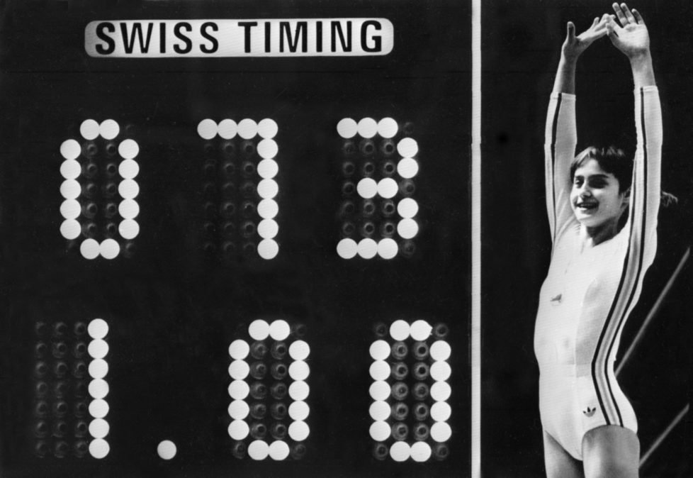 Rumanian champion Nadia Comaneci, aged 14, jubilates when scoreboard shows the perfect score of 10 during Olympic Games 19 July 1976 in Montreal after her acrobatic compulsory at uneven bars. She was awarded with ten points in two exercices and captured 3 gold medals (beam, uneven bars and general competition). Legendary gymnast, during her career Nadia Comaneci captured four Olympic gold medals (1976 : beam, uneven bars and general competition - 1980, beam) and was the first to score 10 in her discipline. / AFP PHOTO